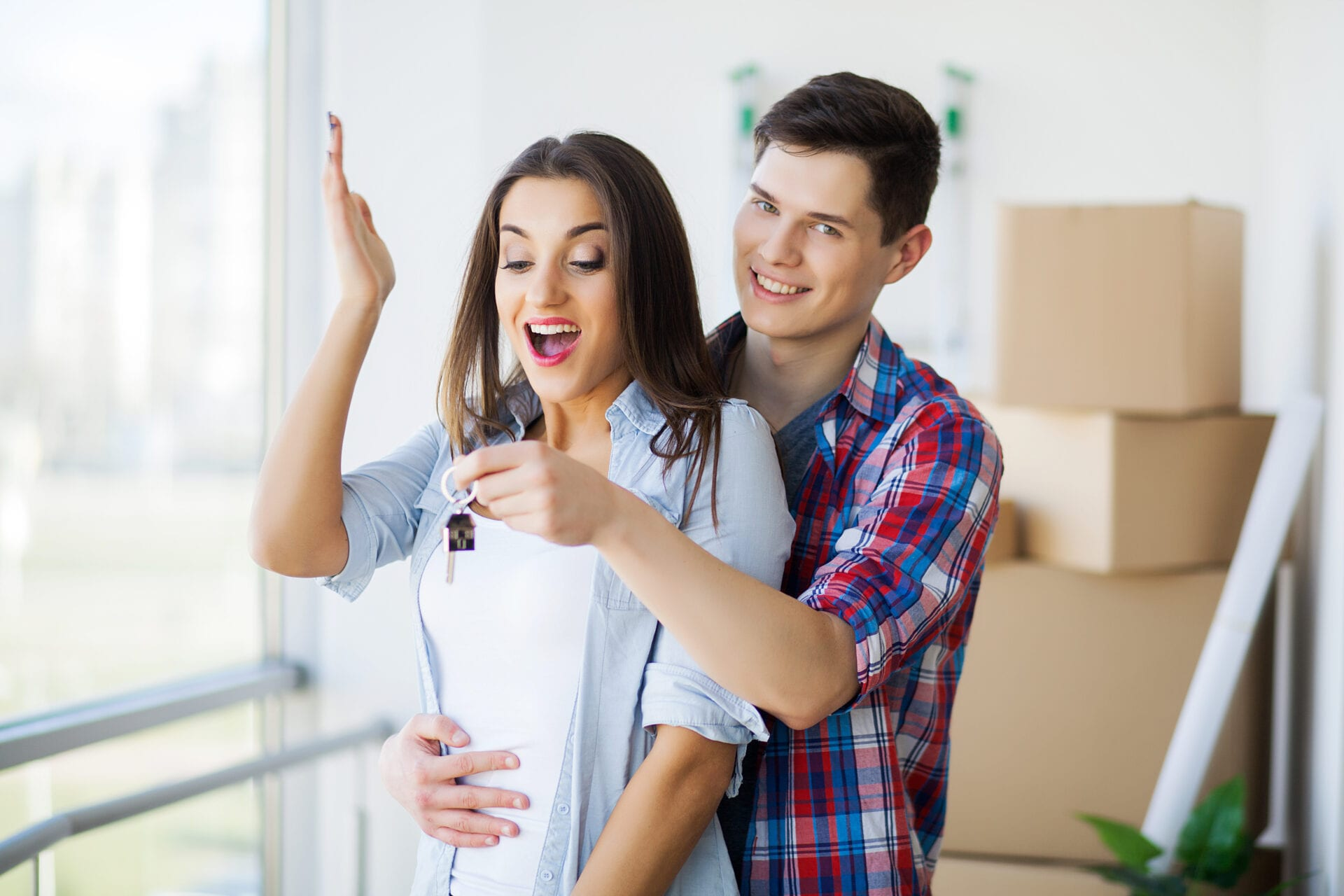 Young Adult Couple Inside Room with Boxes Holding New House Keys Banner.